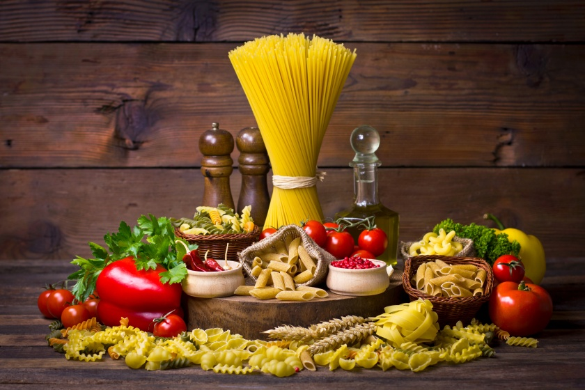 Variety of uncooked pasta and vegetables