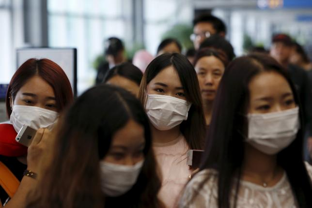 Passengers wearing masks to prevent contracting Middle East Respiratory Syndrome (MERS) walk past a thermal imaging camera (unseen) at Incheon International Airport in Incheon, South Korea, June 2, 2015. REUTERS/Kim Hong-Ji
